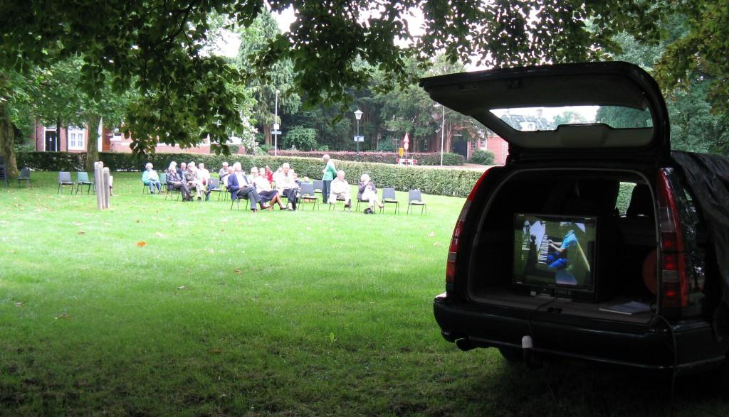 Concert in 2012. Via de draadloze verbinding is de beiaardier op de monitor te zien.