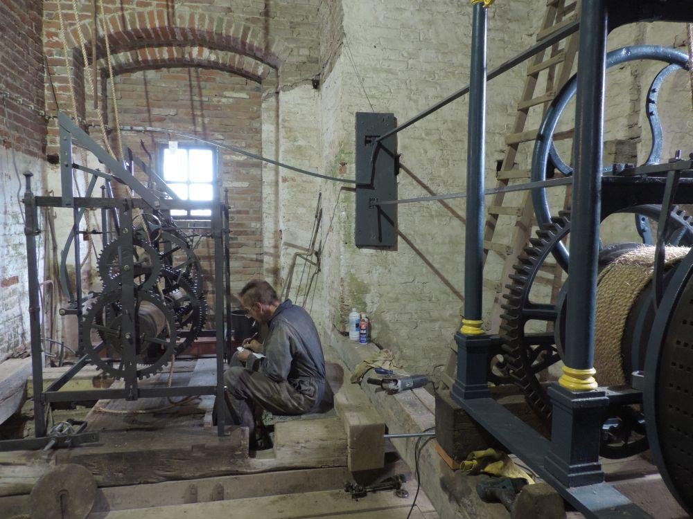 De driehoeken boven op het uurwerk zijn in de 19e eeuw er op gezet om met een stangenstelsel de speeltrommel te activeren.