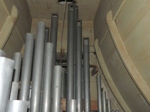 De stang gaat tussen de pijpen van het orgel door.